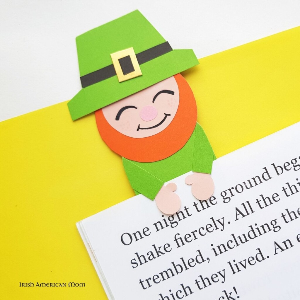 Paper leprechaun with green hat holding a book page by his hands