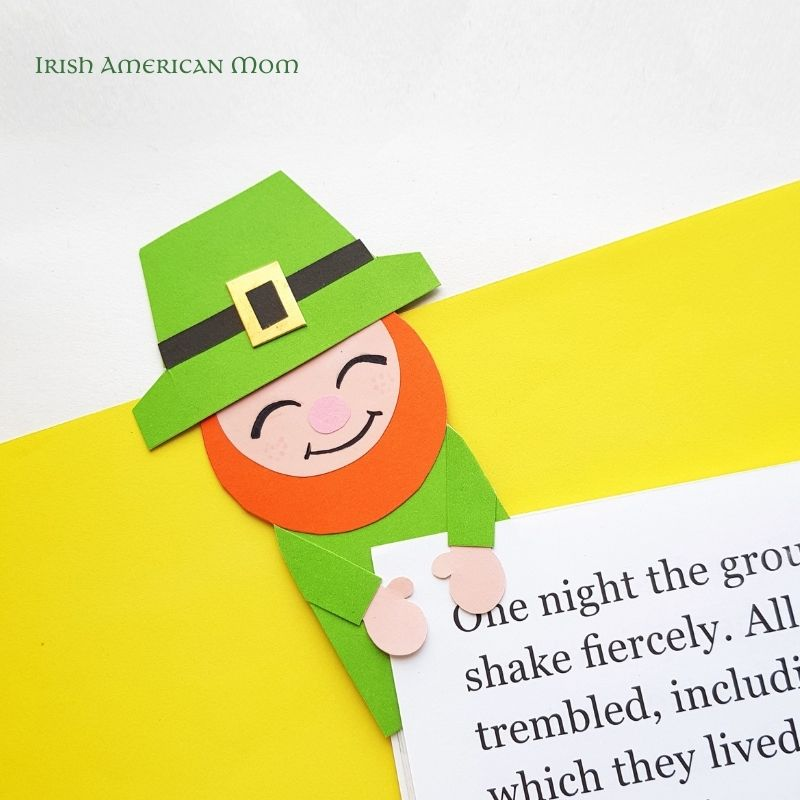 Paper leprechaun bookmark attached to a book page