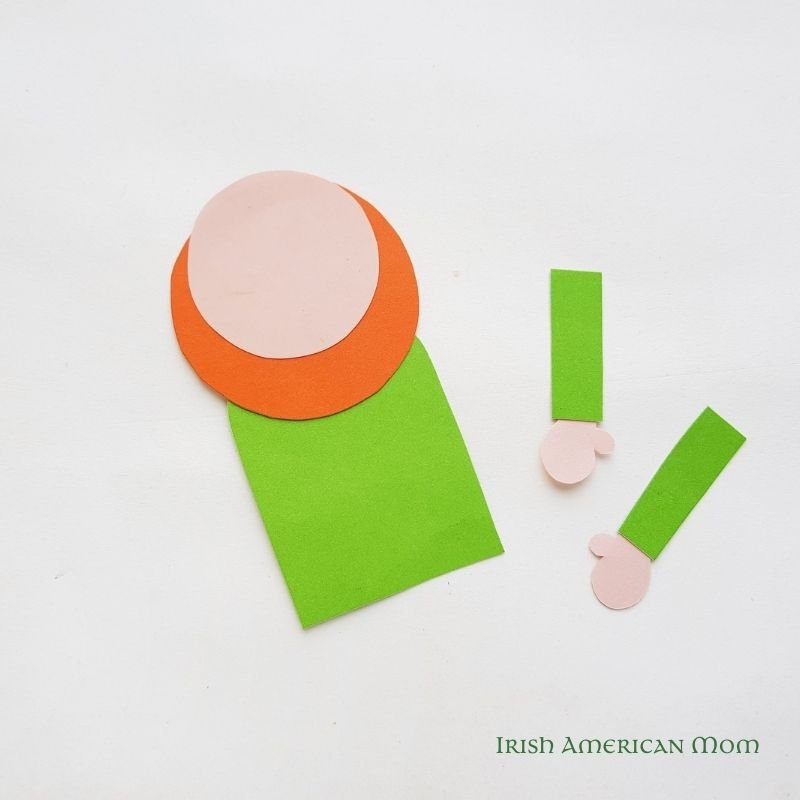 Pink and orange paper circles on to pf a green paper rectangle beside paper arms with pink hands