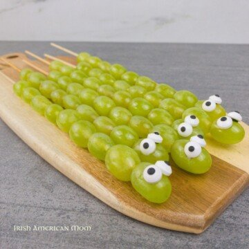 Candy eyed snakes made with grapes on skewers displayed on a cutting board