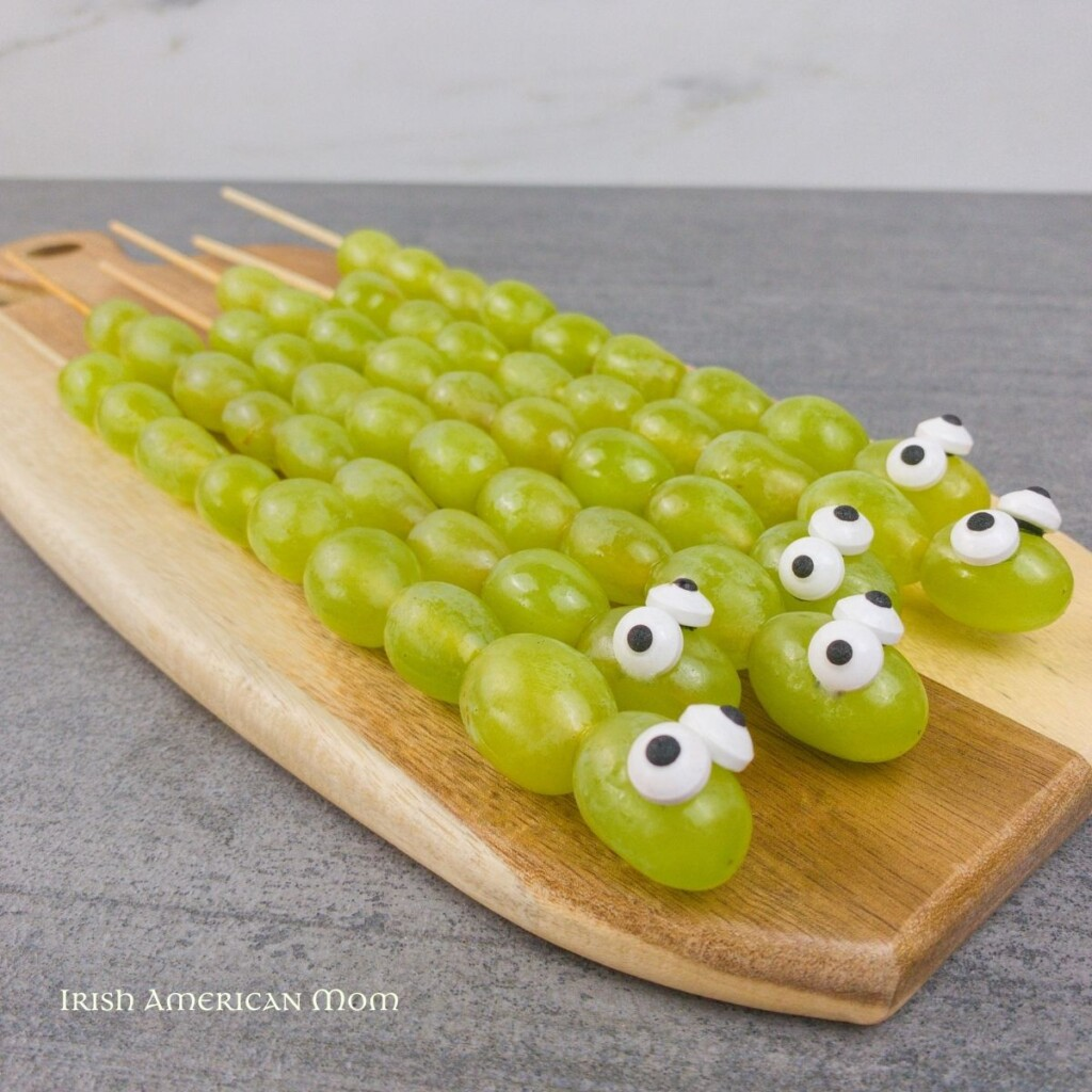 Green grape snakes with candy eyes on a cutting board