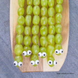 Grape snakes with candy eyes side by side on a cutting board