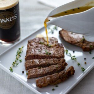 Pouring sauce over a cooked sliced steak beside a glass of Guinness
