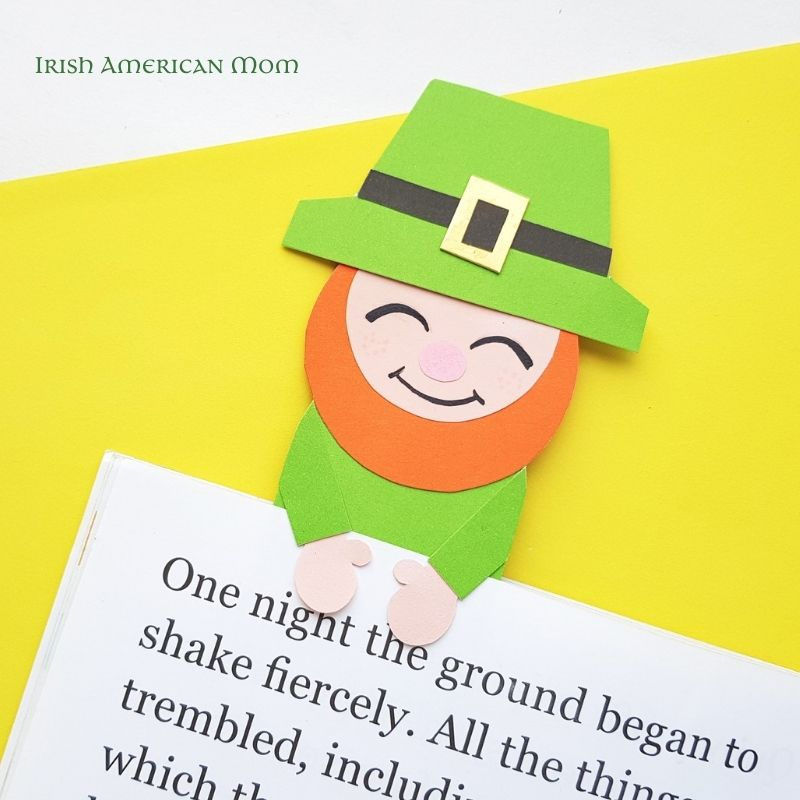 A green leprechaun paper craft bookmark on a page