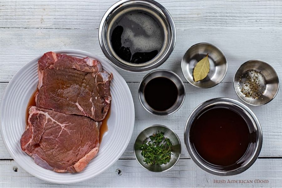 Steak, Guinness, beef broth, thyme, Worcestershire sauce and a bay leaf in dishes and seen from above