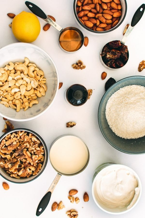 Bowls of nuts, coconut, yogurt, coconut milk, raspberries and syrup