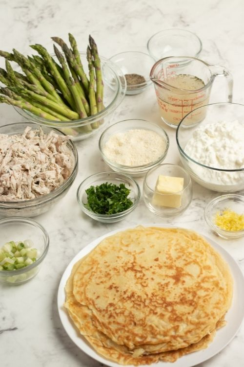 Bowls of asparagus, chicken cheeses and herbs beside a plate of crepes