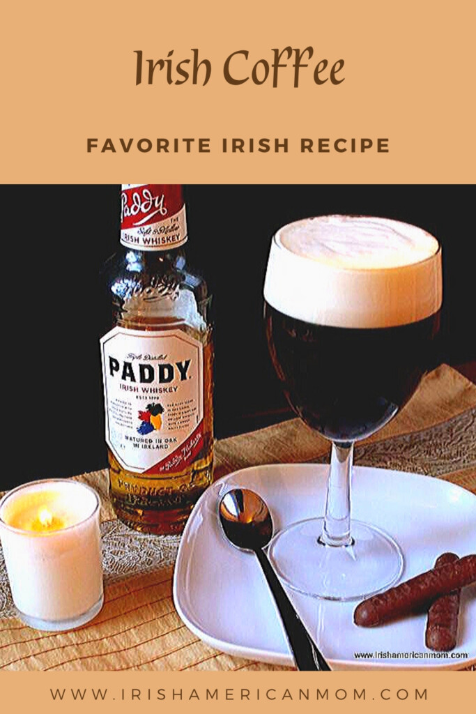 Irish Coffee in a glass with a bottle of whiskey, a candle, and a spoon on a plate with chocolate finger cookies between text banners
