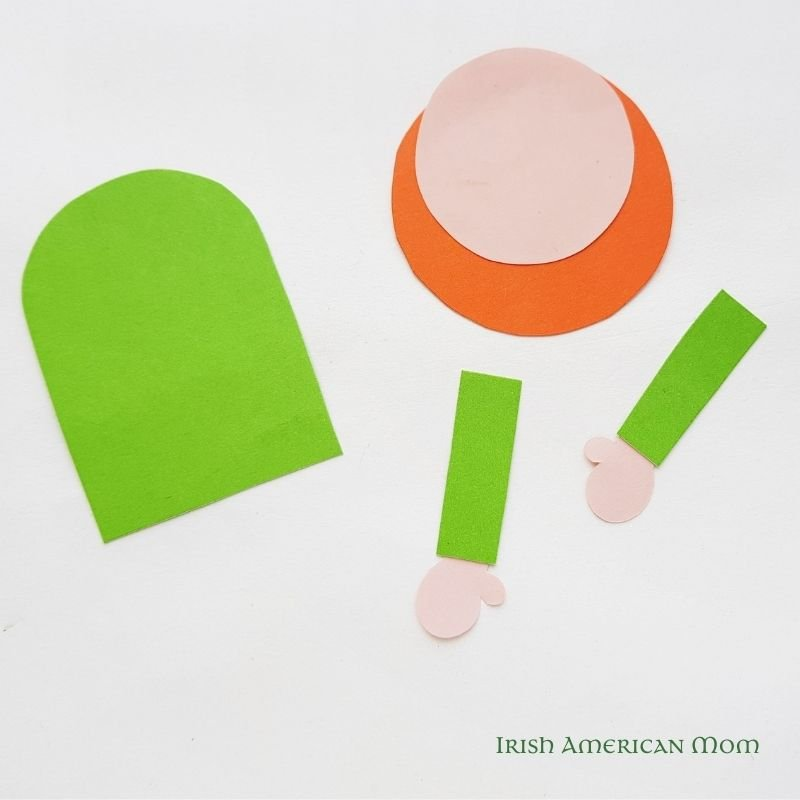 Green arch shape, pink and orange circles, and paper arms