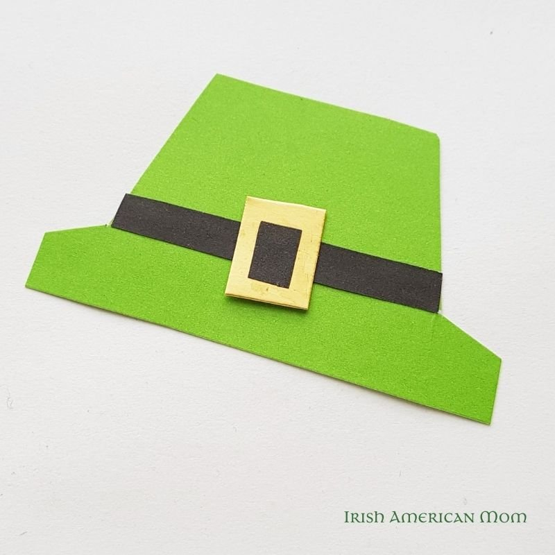 A green paper leprechaun hat with black ribbon and buckle