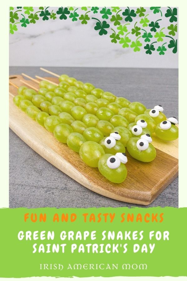 Green grapes on skewers to look like snakes on a graphic with text banner and shamrocks