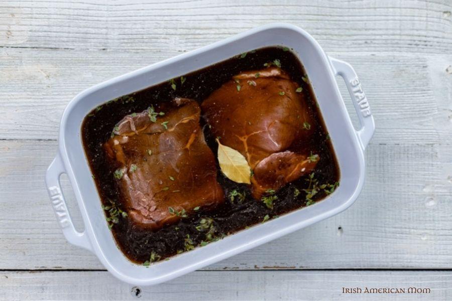 Steak in a casserole soaking in a brown marinade