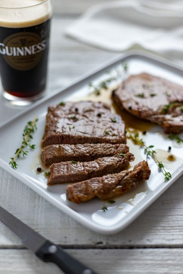 Sliced steaks with Guinness sauce beside a glass of black stout