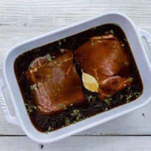 Steaks marinating in a brown liquid in a casserole dish