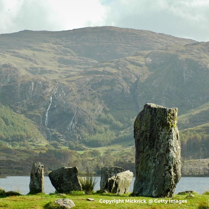 Standing stones at the water's edge with a mountain in the background
