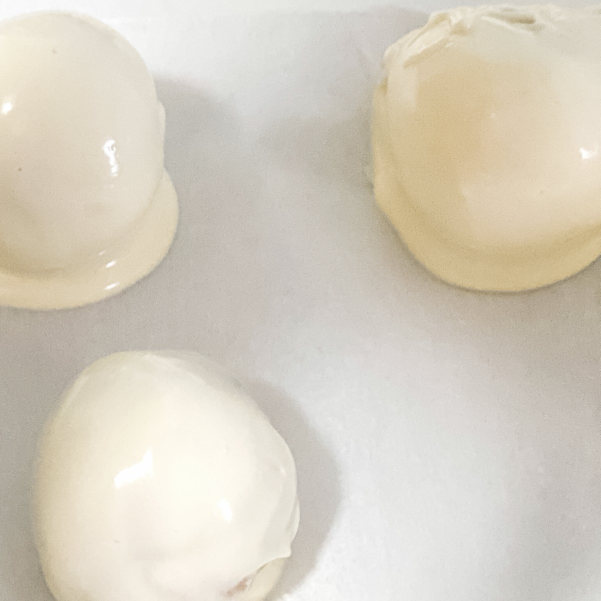 White chocolate covered cake truffles on parchment paper