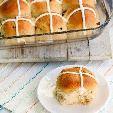A bun with an iced cross on a plate beside a dish of hot cross buns
