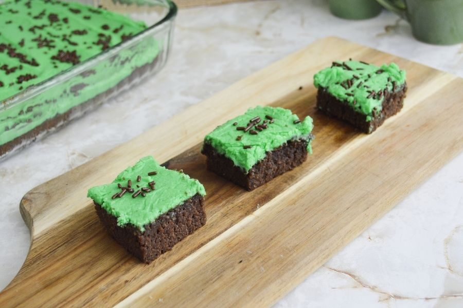 Three Irish brownies with green frosting on a cutting board