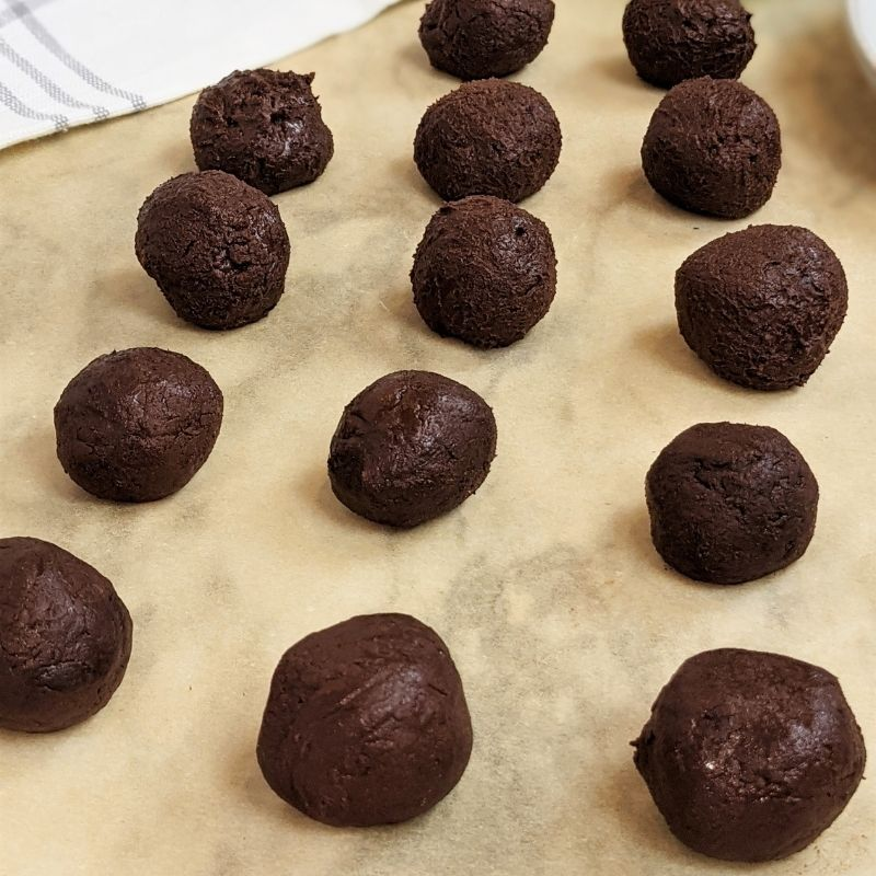 Spheres of chocolate sweets lined up on parchment paper