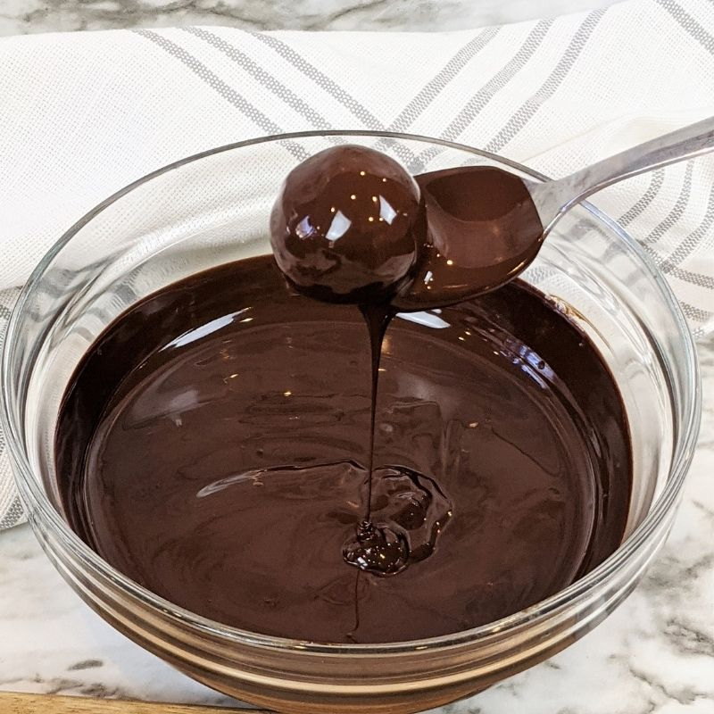 Spoon with a truffle dipping it in melted chocolate in a bowl