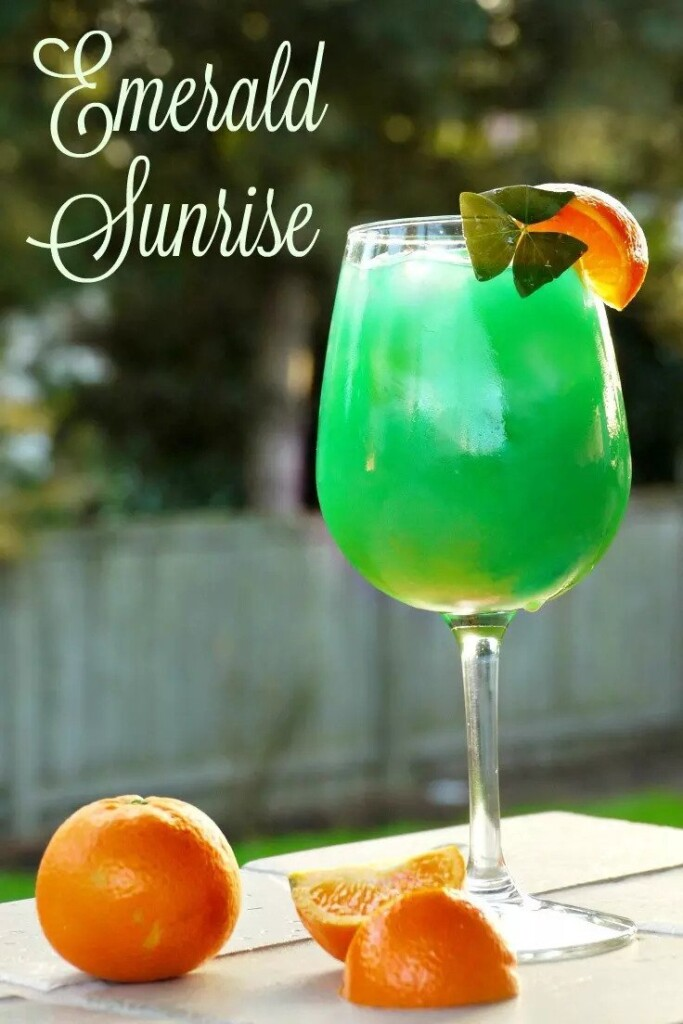 Green cocktail on a table with oranges and text overlay