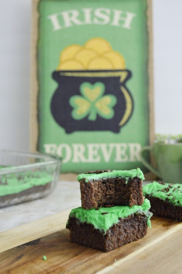 A bite out of an Irish brownie with green frosting in a stack beside a sign with a pot of gold