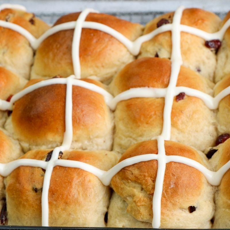 Golden fruit buns with iced crosses on a baking rack