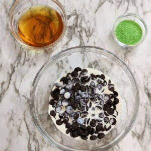 Chocolate chips and cream in a bowl beside a bowl of whiskey and green sprinkles