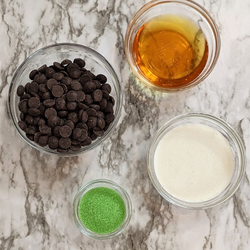 Bowls of chocolate chips, whiskey, cream and green sugar on a marble slab