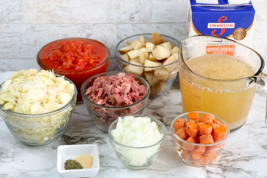 Bowls of cooked cabbage, potatoes, corned beef, diced tomatoes, carrots onions and broth