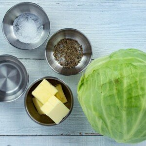 Head of cabbage with butter, water, salt and pepper in ramekins