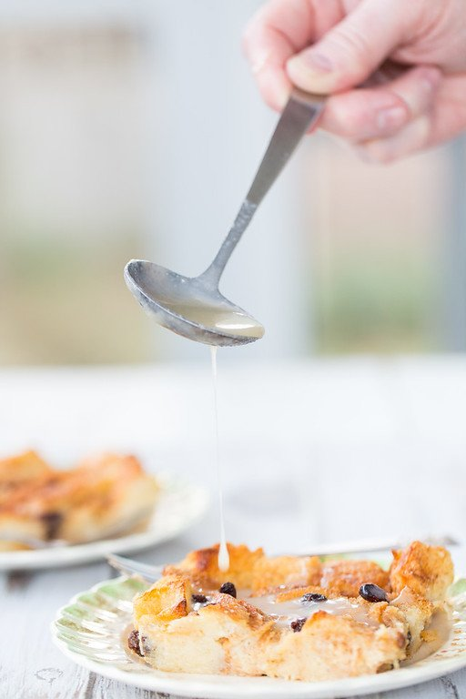 Pouring sauce over bread pudding with a spoon