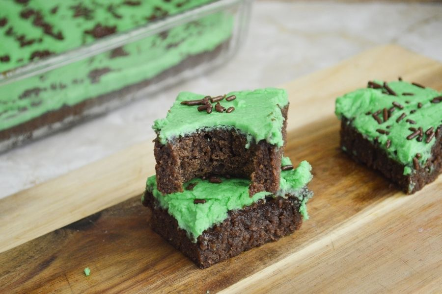 Brownies with green frosting and chocolate sprinkles on a cutting board