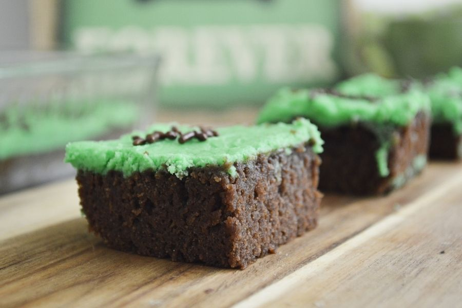 Brownie squares with green frosting and chocolate sprinkles