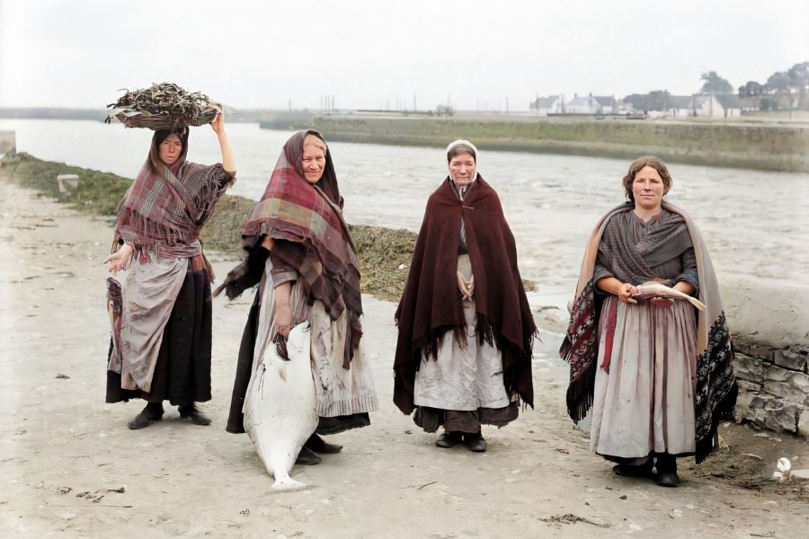 Women wearing shawls and holding fish beside a quay
