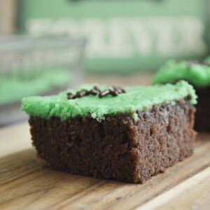 Brownie with green frosting on a wooden board
