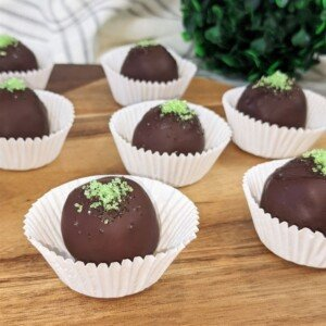 Irish whiskey chocolate truffles with green sprinkles in cupcake paper cases on a cutting board