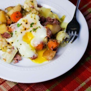A platter of corned beef and potato hash with a soft cooked egg