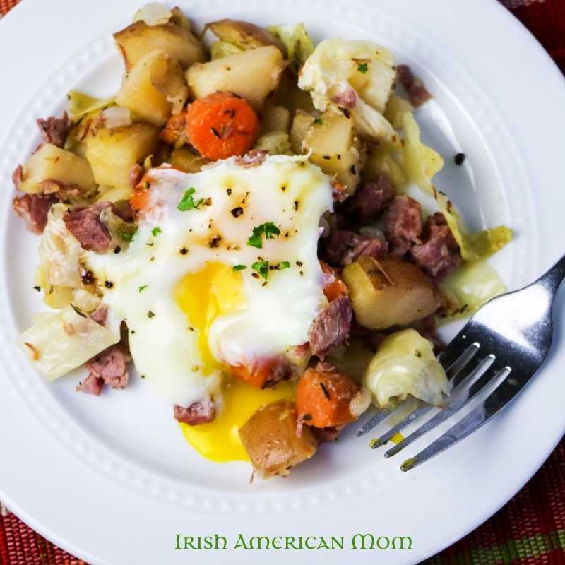 Corned beef hash with a soft cook egg on a white plate with a fork