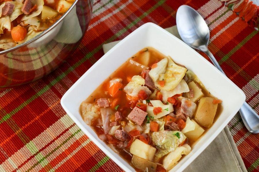 A square bowl of hearty corned beef and vegetable soup