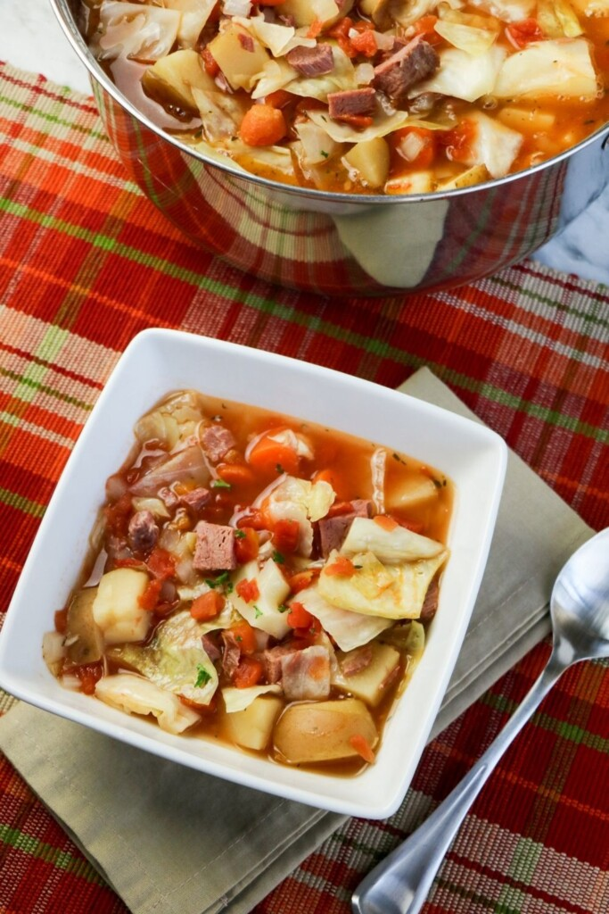 A pot of hearty soup beside a serving in a square bowl