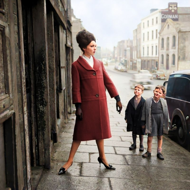 A woman in a red coat on a street beside two boys