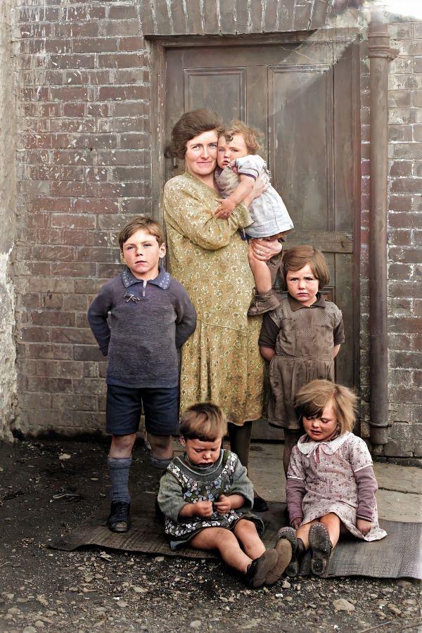 A family posing for a photograph beside a door