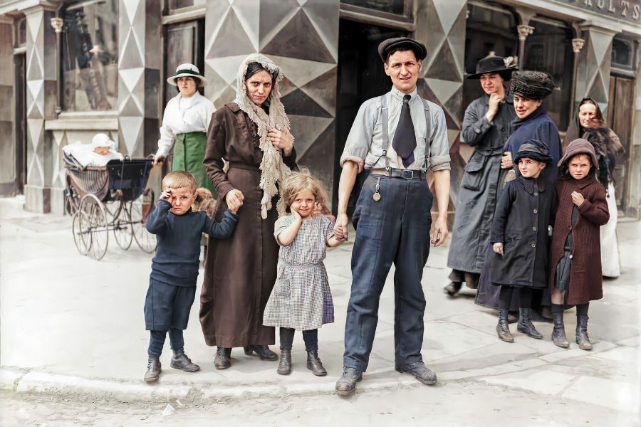 A family wearing vintage clothing on a sidewalk