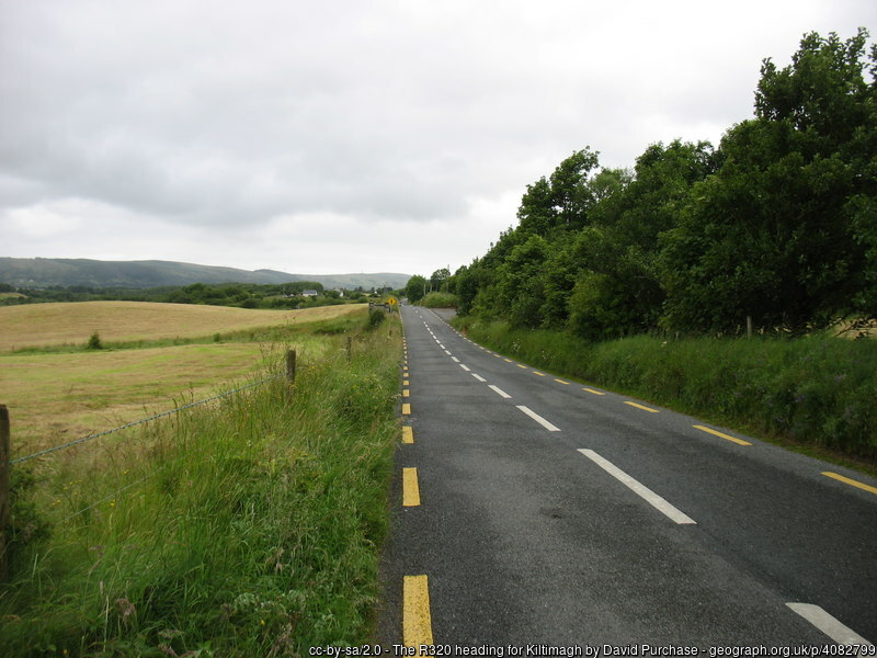 Roadway with fields on one side and trees on the other