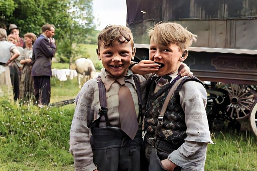 Two boys in a field with a group of people and a caravan