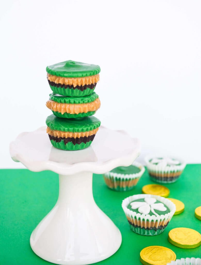 Green peanut butter cups stacked on a cake stand