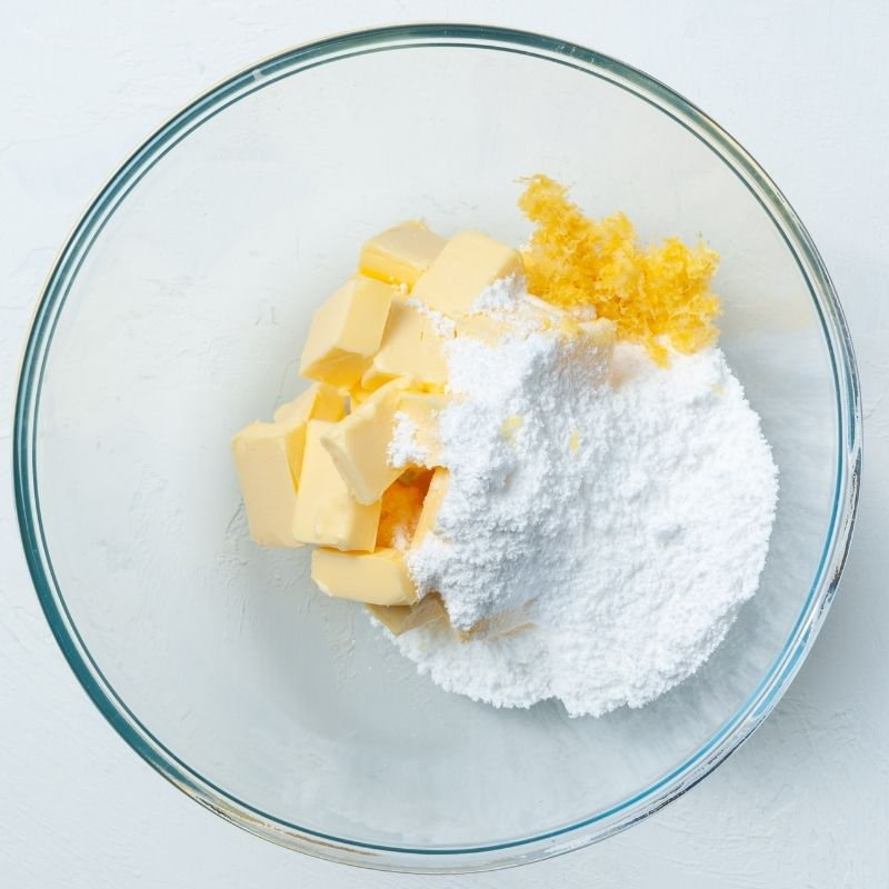 Cubes of butter, powdered sugar and lemon zest in a glass bowl