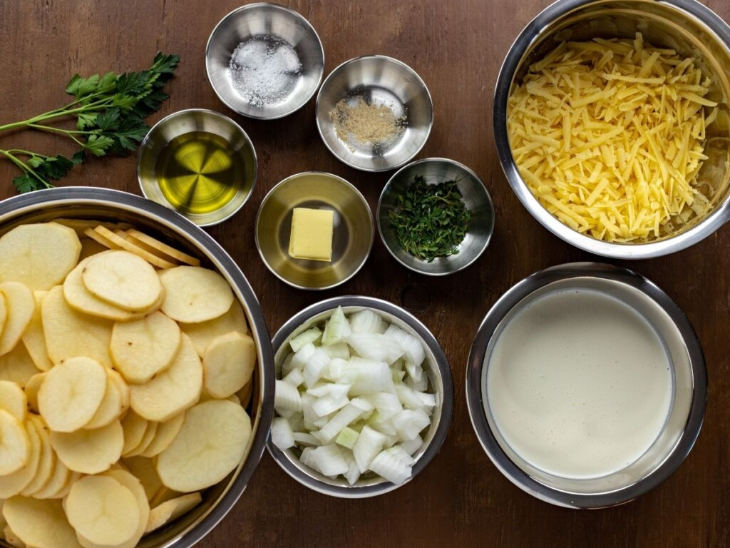 Sliced potatoes, grated cheese cream and other ingredients in bowls for making scalloped potatoes
