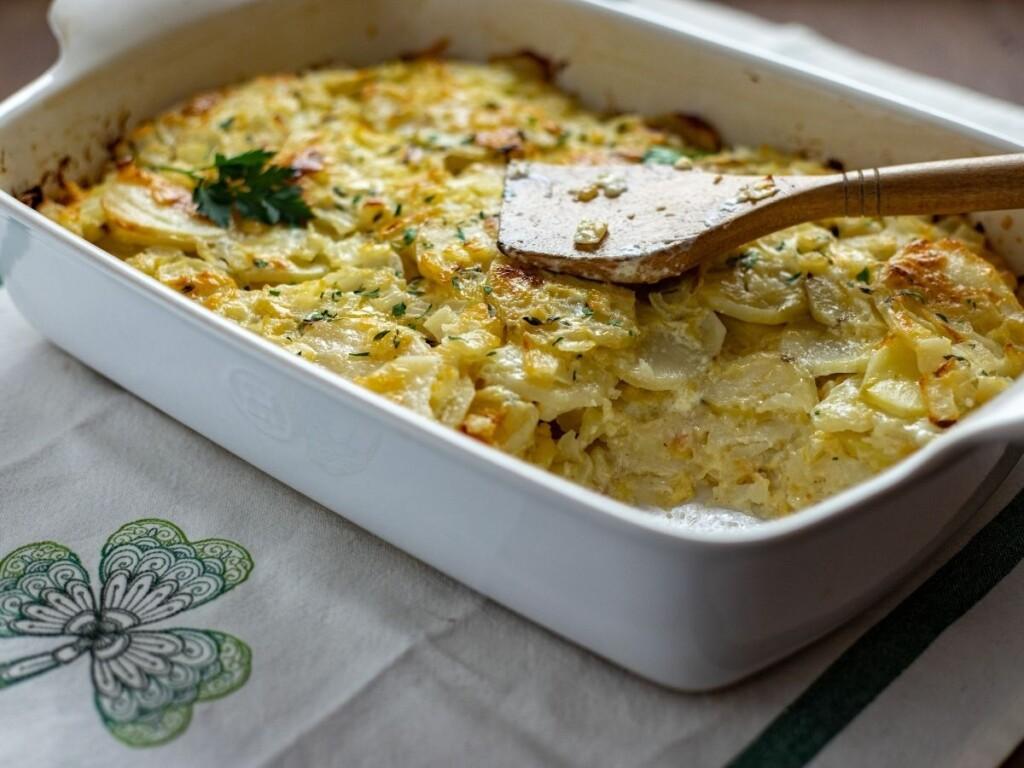 A casserole of cheesy scalloped potatoes on a shamrock dish towel